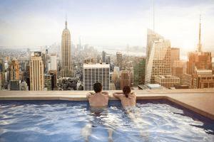 Dos personas miran el 'skyline' de Manhattan desde la piscina de un hotel. / Alija