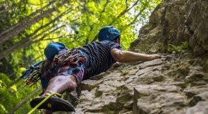 Un deportista asciende por una pared rocosa.